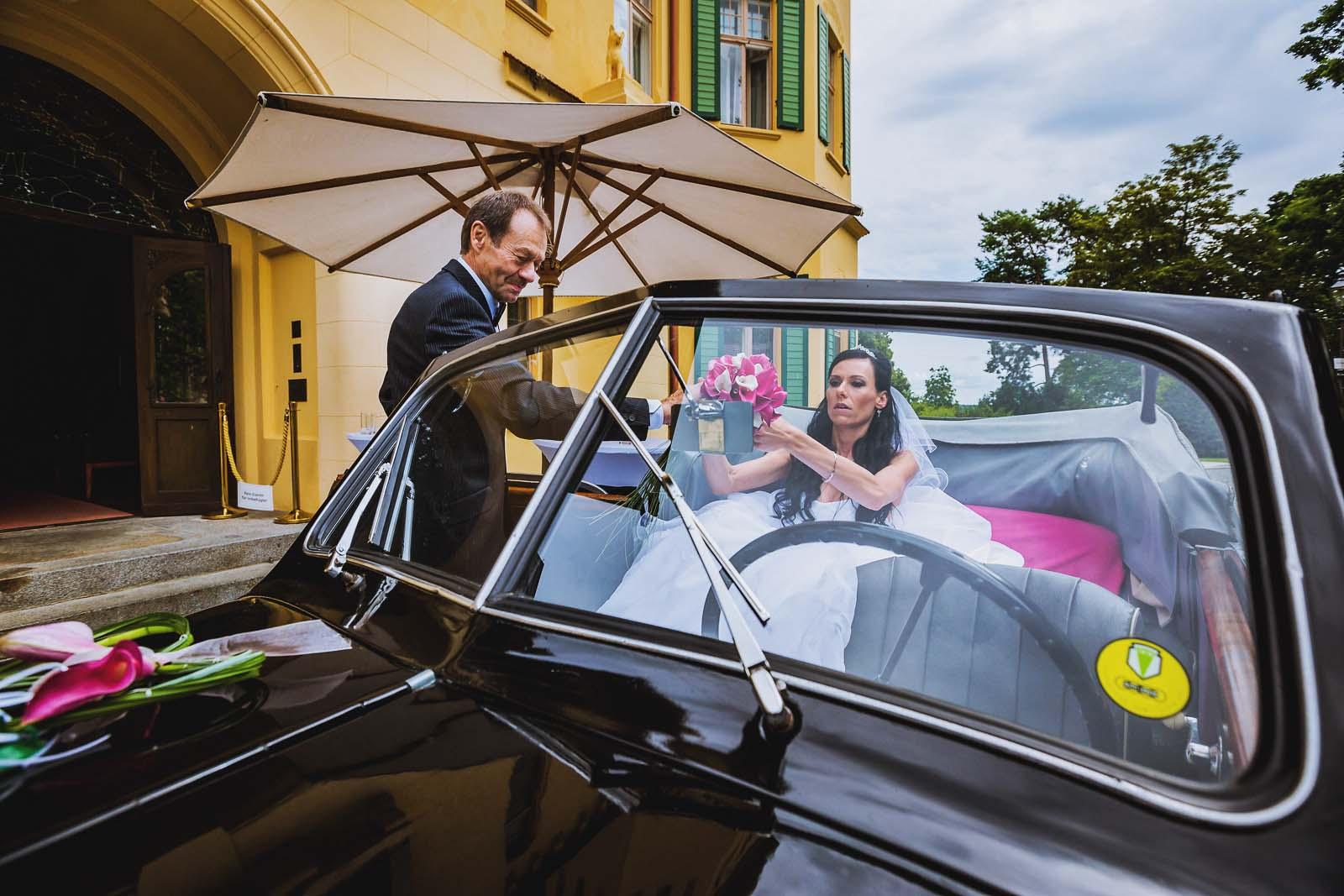 Braut im Hochzeitsauto auf dem Weg zur Hochzeit auf Schloss Hubertushoehe Copyright by Hochzeitsfotograf www.berliner-hochzeitsfotografie.de
