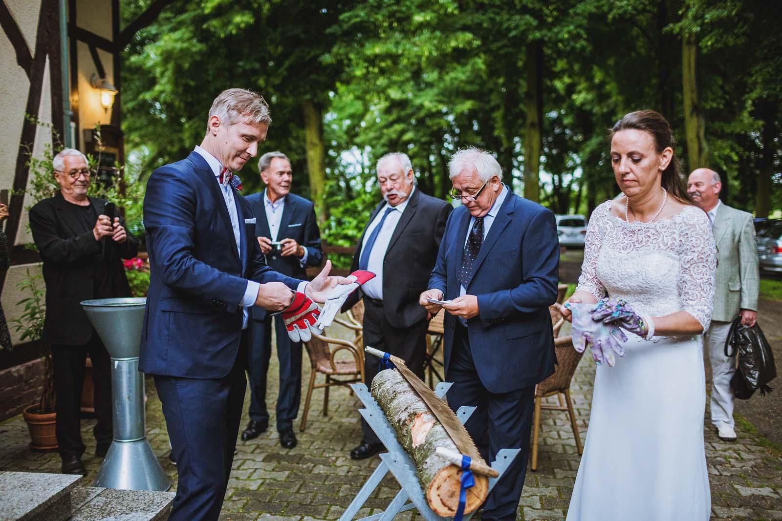 Brautpaar vor dem Baumstammsaegen Hochzeitsfotograf Luebben im Spreewald Copyright by Hochzeitsfotograf www.berliner-hochzeitsfotografie.de