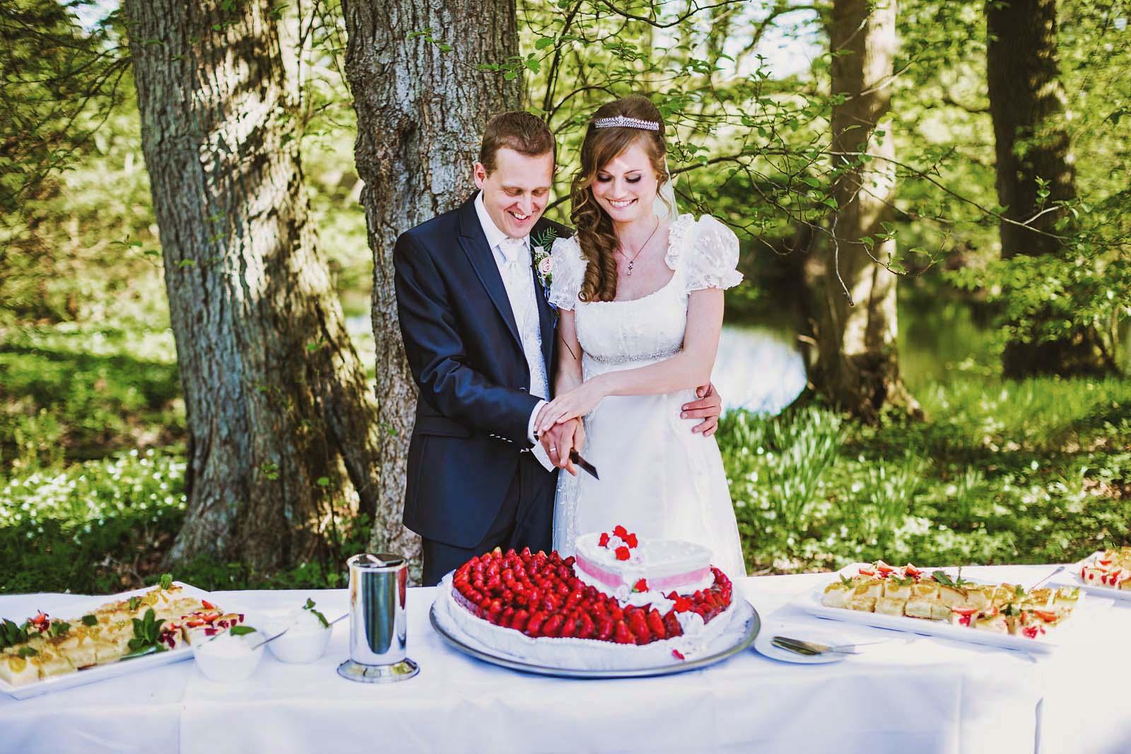 Brautpaar beim Anschnitt der Hochzeitstorte im Gutshaus Kubbelkow Copyright by Hochzeitsfotograf www.berliner-hochzeitsfotografie.de
